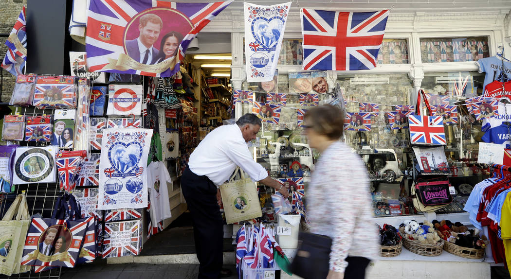 A woman passes a shop window decorated with wedding memorabilia in Windsor, England, Monday, May 14, 2018. Preparations are being made in the town ahead of the wedding of Britain's Prince Harry an ...