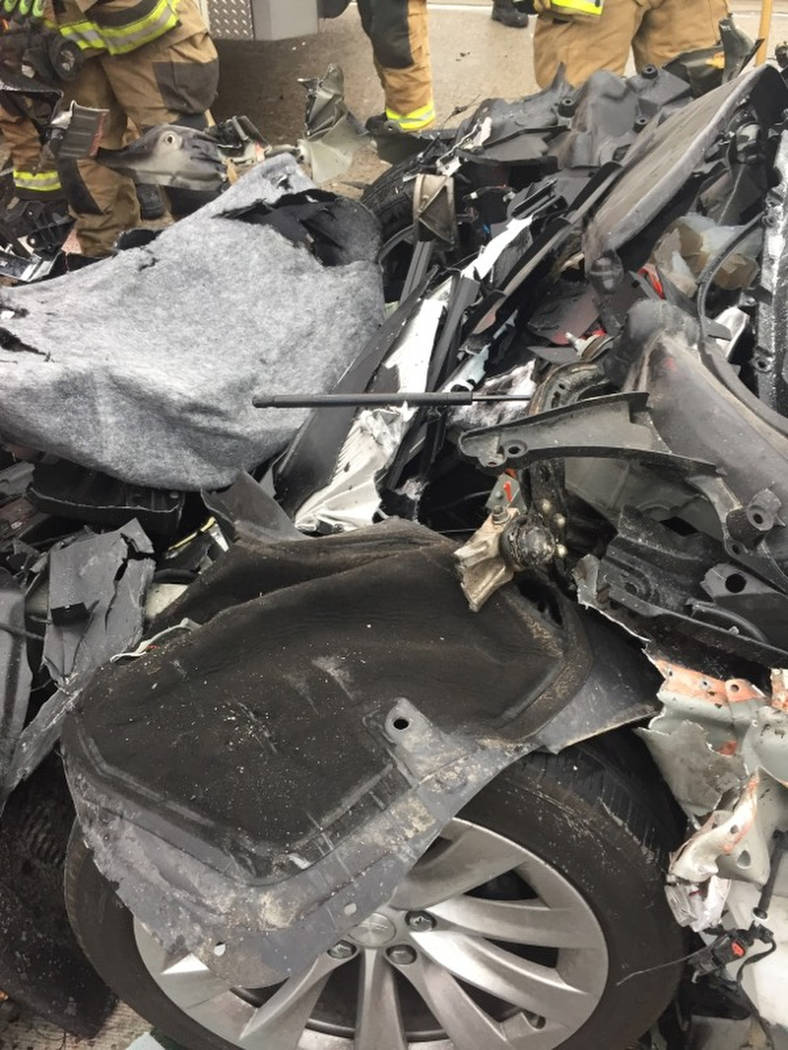 In this Friday, May 11, 2018, photo released by the South Jordan Police Department shows a traffic collision involving a Tesla Model S sedan with a Fire Department mechanic truck stopped at a red ...