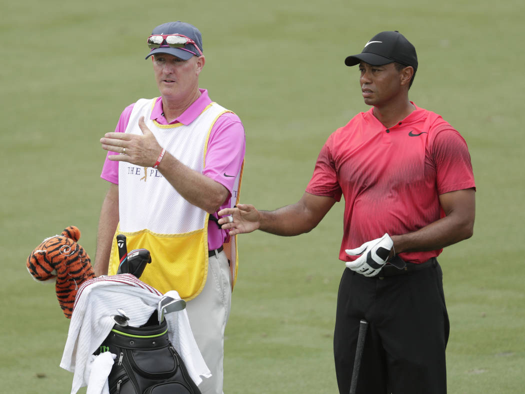 Tiger Woods and his caddie Joe Lacava, look down the third fairway, during the final round of The Players Championship golf tournament, Sunday, May 13, 2018, in Ponte Vedra Beach, Fla. (AP Photo/L ...