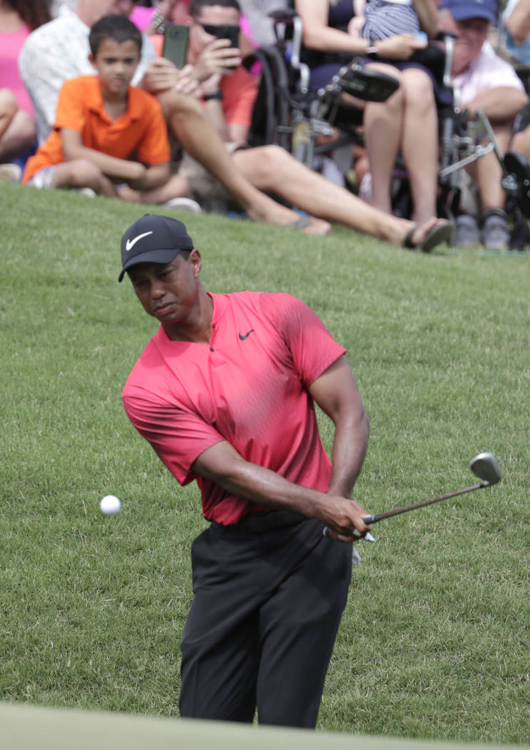 Tiger Woods makes a chip shot onto the ninth green, during the final round of The Players Championship golf tournament, Sunday, May 13, 2018, in Ponte Vedra Beach, Fla. (AP Photo/Lynne Sladky)