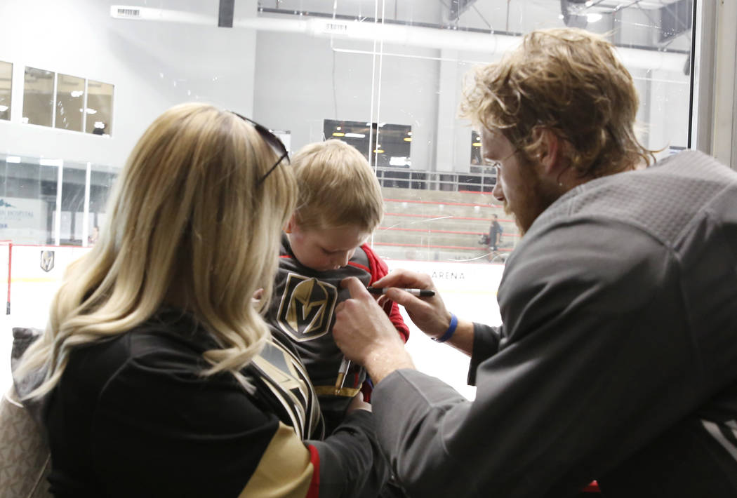 Samantha Gaston watches as Golden Knights defenseman Jon Merrill signs autograph on her son Declan Gaston's, 2, jersey after optional team practice at City National Arena on Tuesday, May 15, 2018, ...
