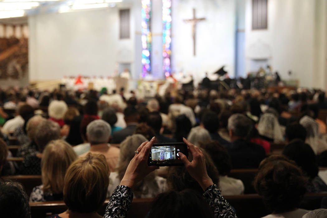 A woman takes a photos during the installation ceremony of Rev. George Leo Thomas as the third Bishop of Las Vegas, at The Shrine of the Most Holy Redeemer in Las Vegas, Tuesday, May 15, 2018. Eri ...