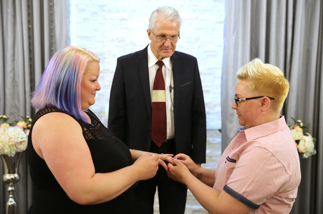 Tara, left, and Allie Shima of Stateline exchange rings during their wedding with officiant Richard Nielson at Vegas Weddings chapel in downtown Las Vegas Thursday, May 17, 2018. K.M. Cannon Las V ...