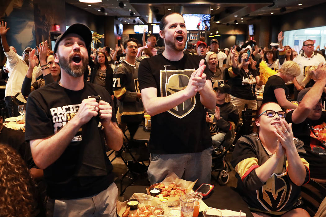 From left, Dustin Abell, Jackson Loless and Jennifer Anderson, all of Las Vegas, cheer after the Vegas Golden Knights score against the Winnipeg Jets during the second game of the Western Conferen ...