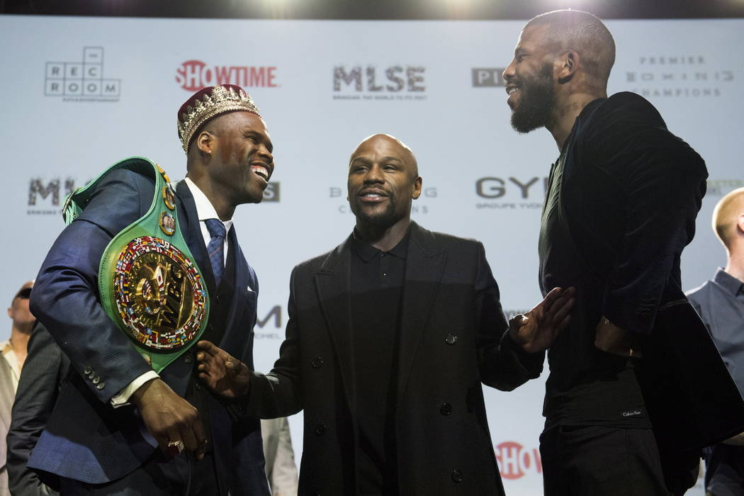 WBC light heavyweight title holder Adonis Stevenson, left, co-promoter Floyd Mayweather, center, and challenger Badou Jack pose for a photo after a boxing press conference at the Rec Room in Toron ...