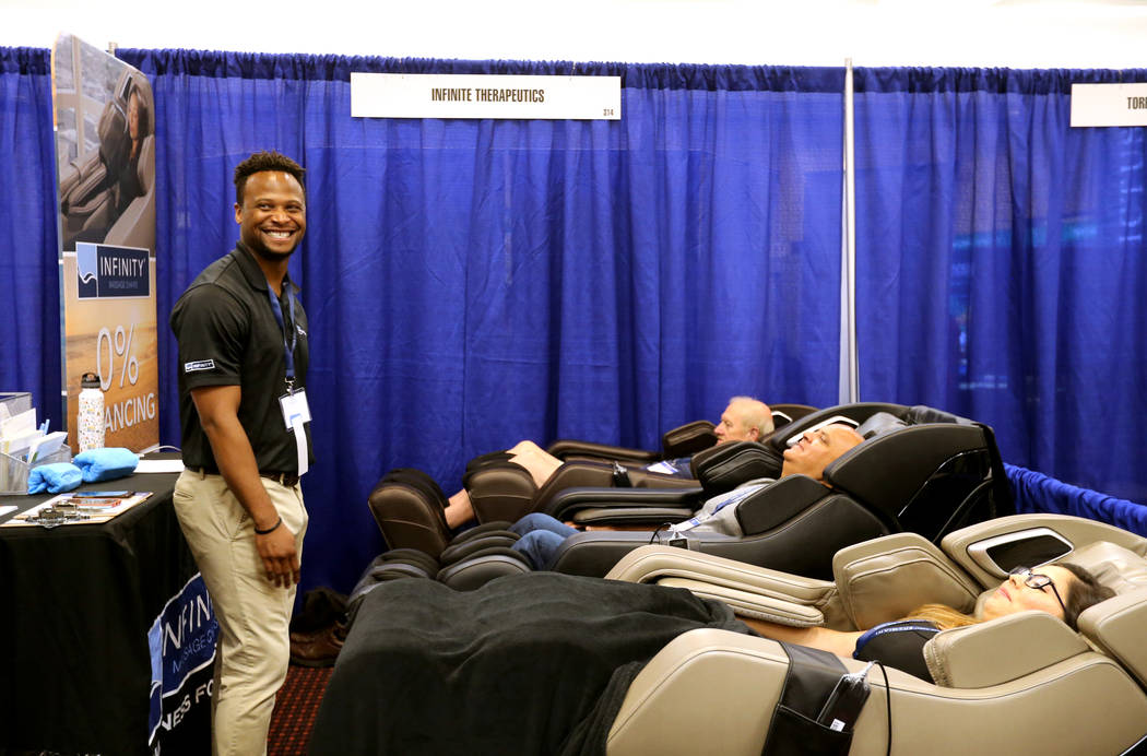 Joshua Tiggs of Infinity Massage Chairs, left, gives demonstrations to, from right, Jazmin Lopez, Paul Mann, both of Canada, and Philip Evans of Kilmarnock, Va. at The MoneyShow Las Vegas at Bally ...