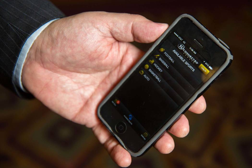 Bob Scucci, Boyd Gaming's director of race and sports books, holds his phone launched with B Connected Sports, a sports wagering application for mobile devices, at The Orleans Friday, Sept. ...
