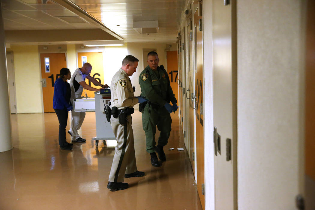 Correction officers K. Camp, left, and R. Fitzgerald visit inmates with medical staff to distribute medication, during a tour of the Clark County Detention Center on the Stepping Up Day of Action, ...