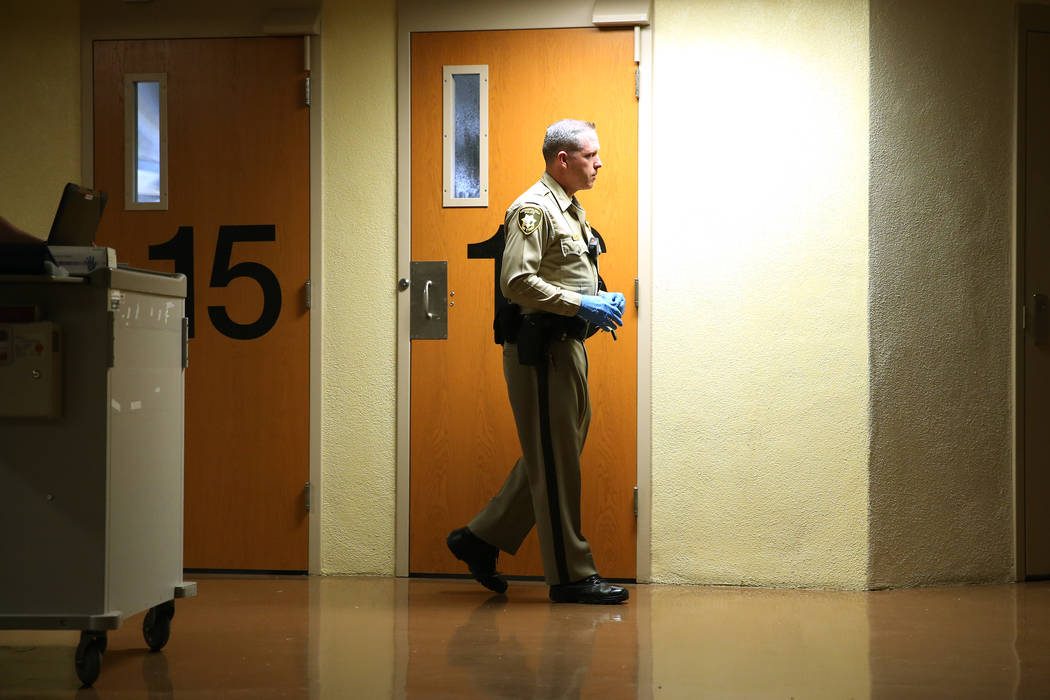 Correction officer K. Camp visits inmates with medical staff, not pictured, to distribute medication, during a tour of the Clark County Detention Center on the Stepping Up Day of Action, Wednesday ...