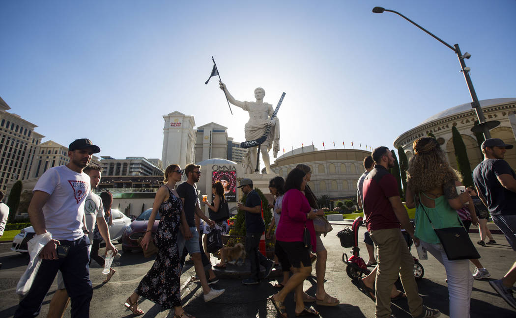 Pedestrians pass by a statue of Julius Caesar adorned with a Golden Knights flag and hockey stick outside of Caesars Palace in Las Vegas on Tuesday, May 15, 2018. Chase Stevens Las Vegas Review-Jo ...