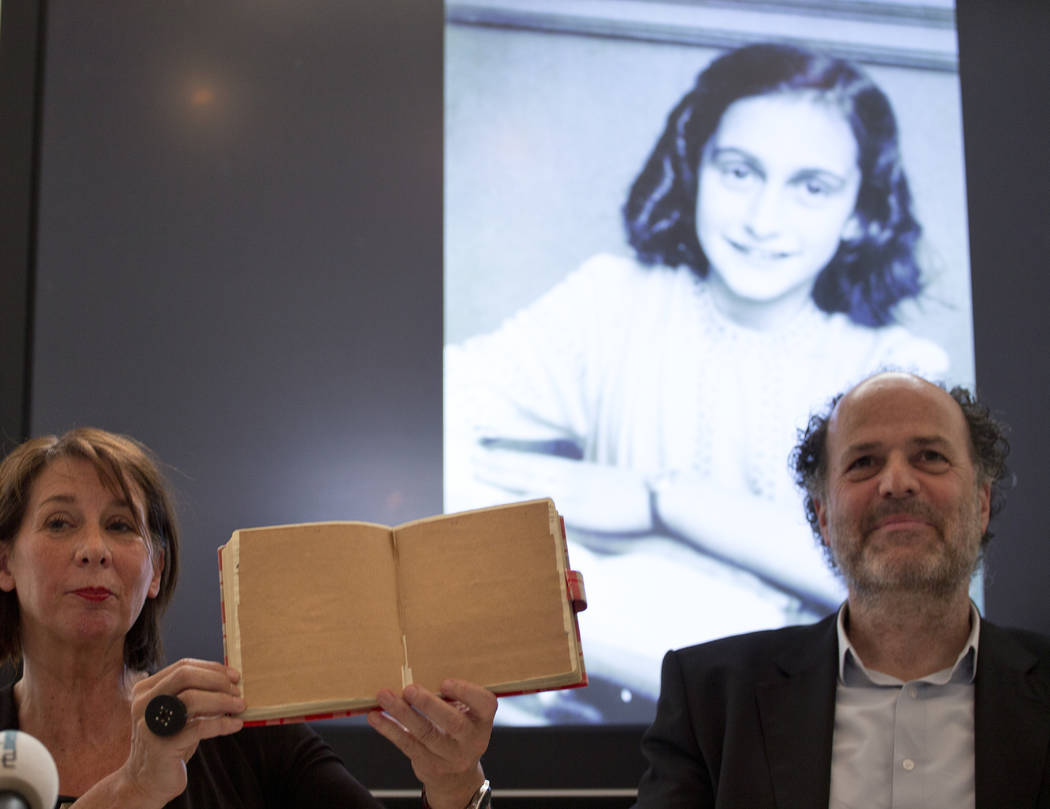 Teresien da Silva, left, and Ronald Leopold of the Anne Frank Foundation show a facsimile of Anne Frank's diary with two pages taped off during a press conference at the foundation's office in Ams ...