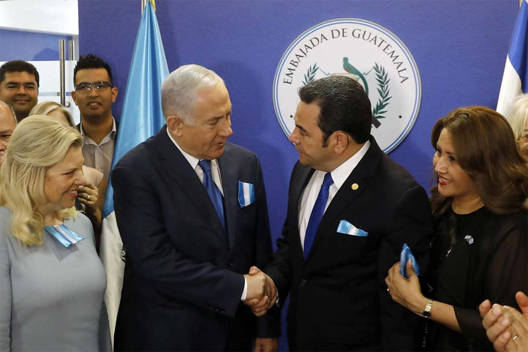 Israel Prime Minister Benjamin Netanyahu, center left, and Guatemala President Jimmy Morales shake hands as their wives, Sara Netanyahu, left, and Hilda Patricia Marroquin look on during the dedi ...