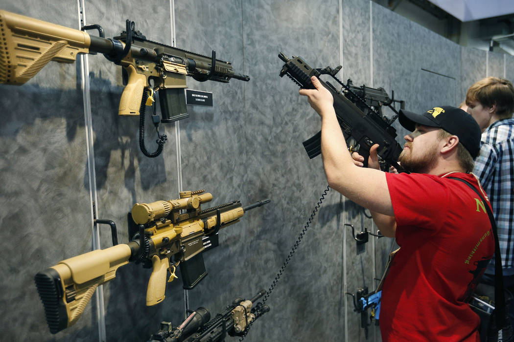 FILE - In this Jan. 19, 2016 file photo, Nolan Hammer looks at a gun at the Heckler & Koch booth at the Shooting, Hunting and Outdoor Trade Show in Las Vegas. Nearly two-thirds of Americans ex ...
