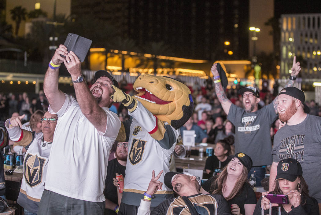 Bernie Lange, left, takes a selfie with Golden Knights mascot Chance after a second period goal at a watch party during game three of Vegas' playoff series with the San Jose Sharks on Monday, Apri ...