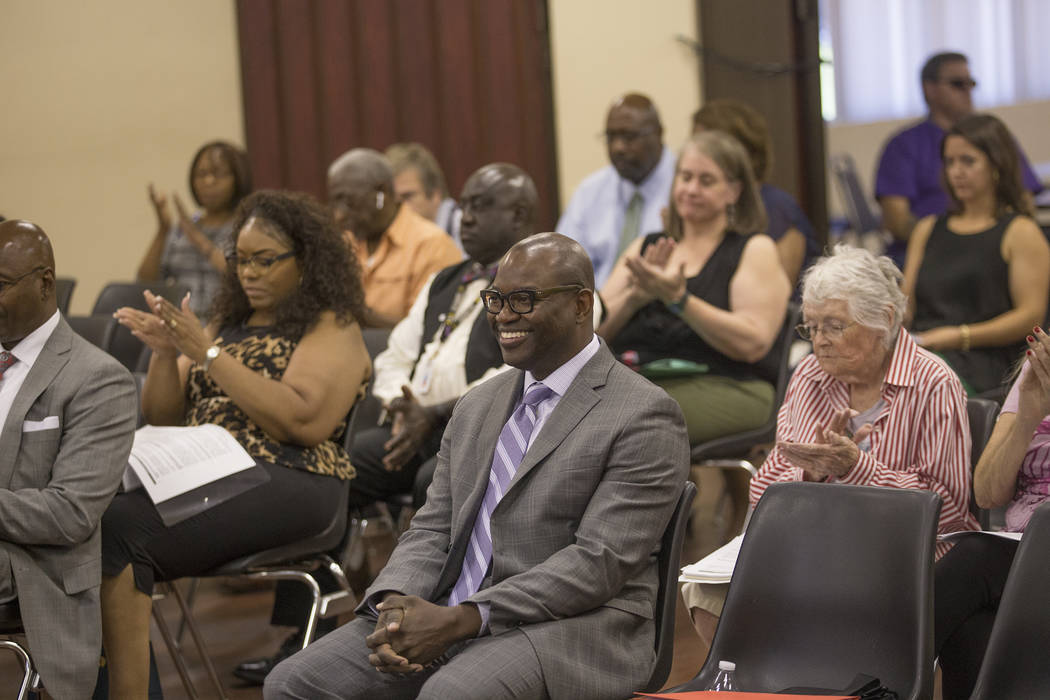 Attendees applaud after the board of commissioners approved Chad Williams, center, as new executive director at the Southern Nevada Regional Housing Authority board meeting at the commission chamb ...
