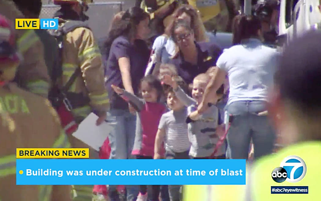 In this photo taken from video provided by KABC-TV, children are evacuated from a preschool across the street from a building that was rocked by an explosion in Aliso Viejo, Calif., Tuesday aftern ...