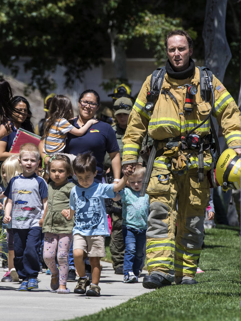 Firefighters and sheriff's deputies escort children from Academy on the Hill pre-k school in Aliso Viejo, Calif., on Tuesday, May 15, 2018, after a fatal explosion nearby. The blast involved a bui ...