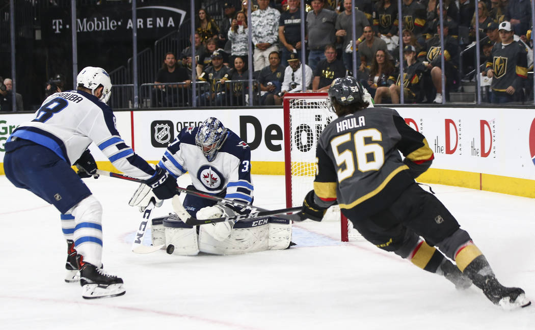 Winnipeg Jets goaltender Connor Hellebuyck (37) blocks a shot from Golden Knights left wing Erik Haula (56) during the first period of Game 3 of the NHL Western Conference finals hockey playoff se ...