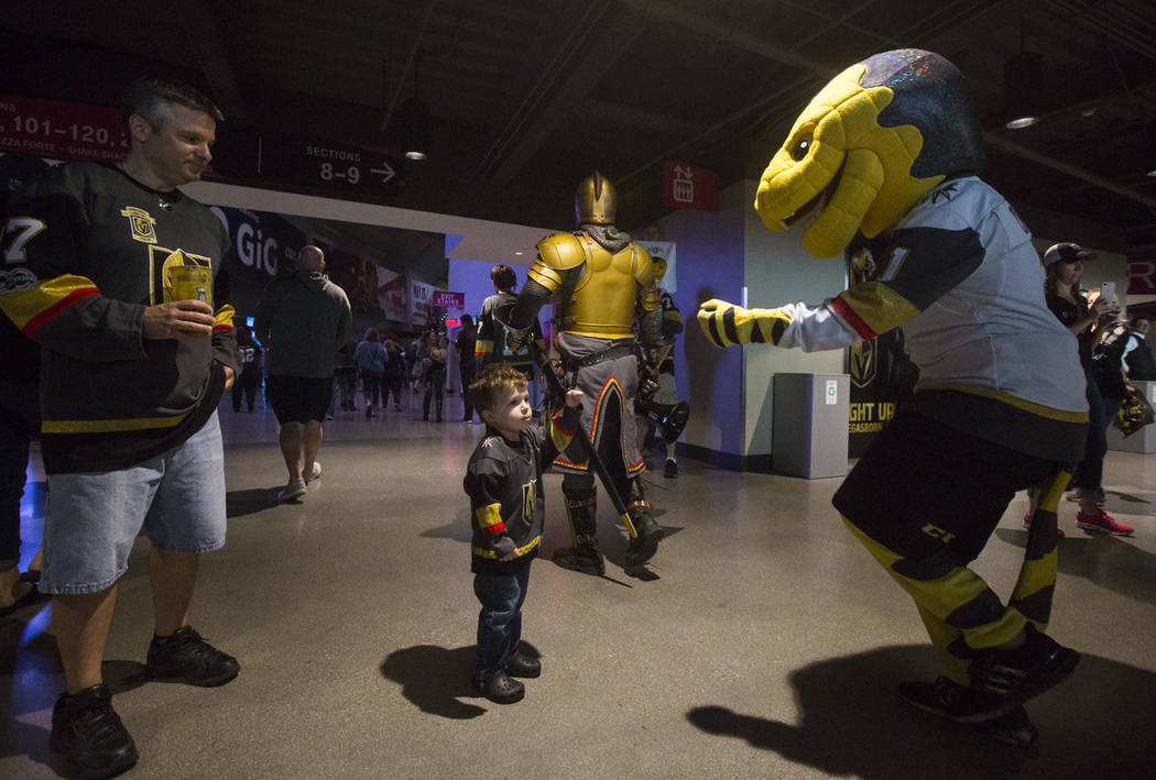Golden Knights mascot Chance fist-bumps 3-year-old Jacob Rietgraf before the start of Game 3 of the NHL Western Conference finals hockey playoff series at T-Mobile Arena in Las Vegas on Wednesday, ...