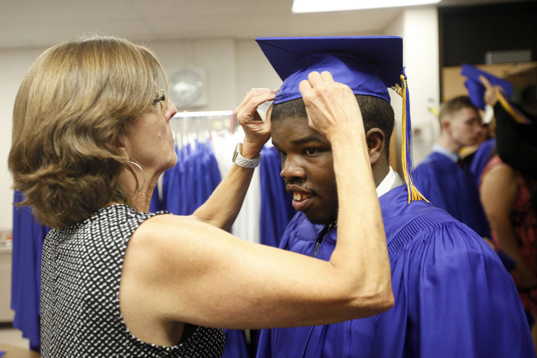 Rachel Kahow helps Anthony Carter-Martin put on his cap at Helen J. Stewart School in Las Vegas, Wednesday, May 16, 2018. The special needs school hosted a graduation ceremony for students. Rachel ...