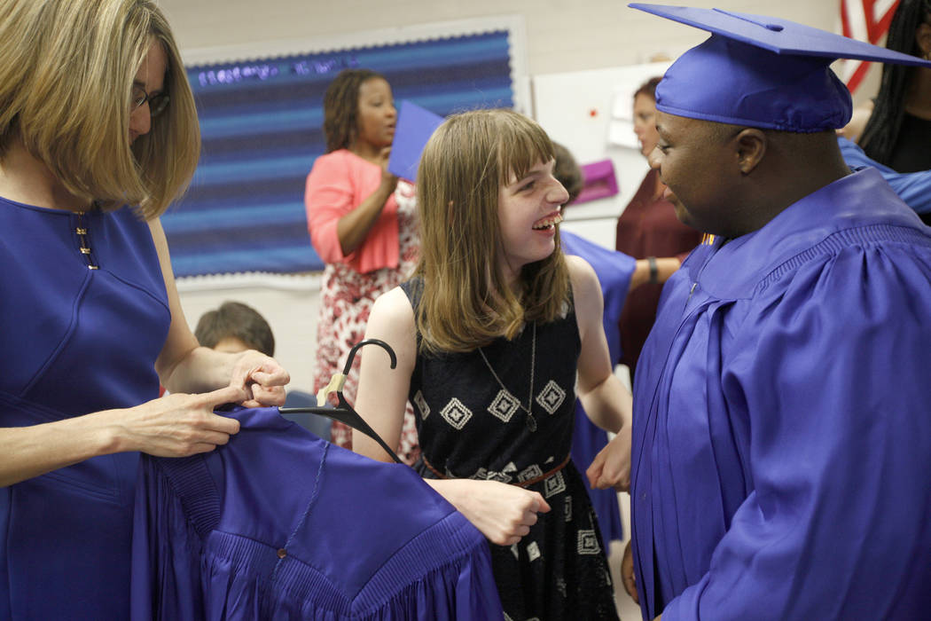 Valerie Brown, left, helps Sydney Goecke as she talks to fellow student Tobby Davis at Helen J. Stewart School in Las Vegas, Wednesday, May 16, 2018. The special needs school hosted a graduation c ...