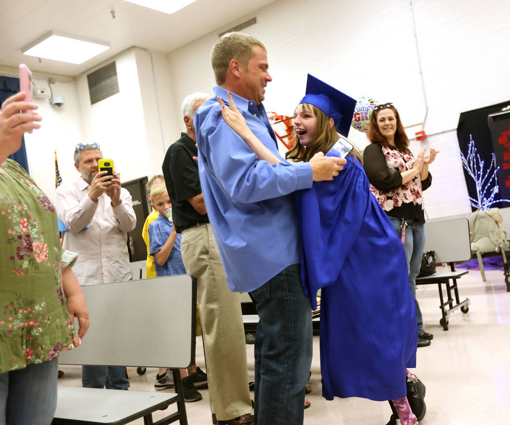 Sydney Goecke runs to hug her dad Jason Goecke on her way down the aisle at Helen J. Stewart School in Las Vegas, Wednesday, May 16, 2018. The special needs school hosted a graduation ceremony for ...