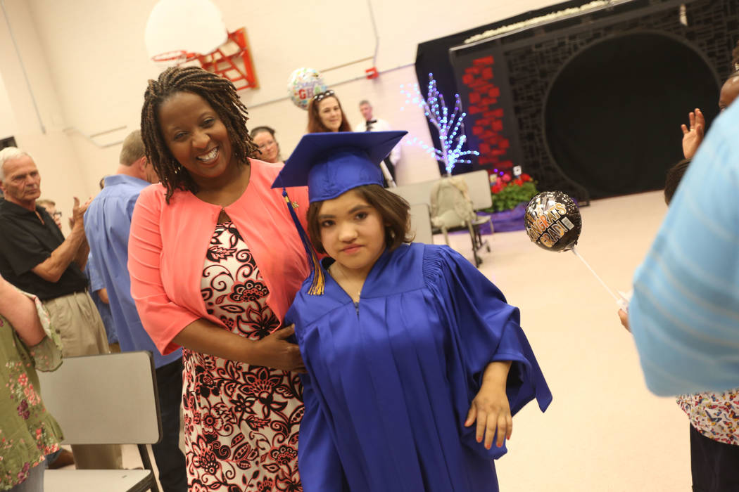 Brenda Rodriguez, assisted by Dawn Euseary, makes her way to the front at Helen J. Stewart School in Las Vegas, Wednesday, May 16, 2018. The special needs school hosted a graduation ceremony for s ...