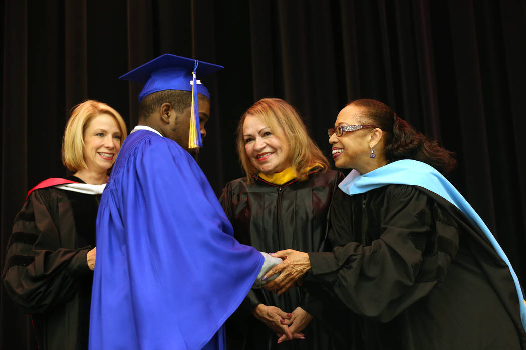 School board trustee Dr. Linda Young congratulates Anthony Carter-Martin as Dr. Deanna Jaskolski, left, and school board trustee Linda Cavazos during a graduation ceremony at Helen J. Stewart Scho ...