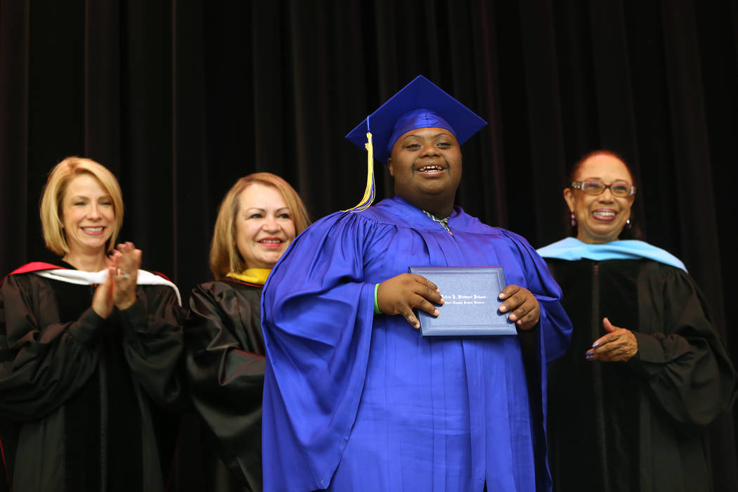 Tobby Davis holds his diploma in front of Dr. Deanna Jaskolski, from left, school board trustee Linda Cavazos, and school board trustee Dr. Linda Young during a graduation ceremony at Helen J. Ste ...