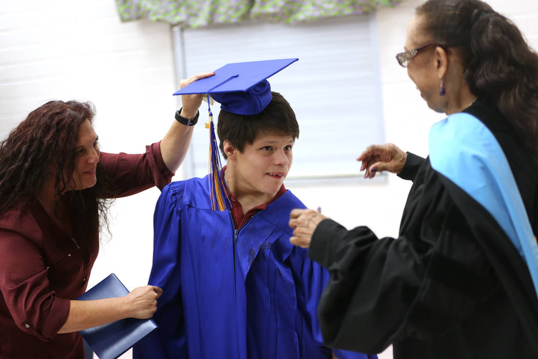 Lynda Greenwald, left, helps Isaiah Milligan keep on his cap before school board trustee Dr. Linda Young changes his tassel over during a graduation ceremony at Helen J. Stewart School, a special ...