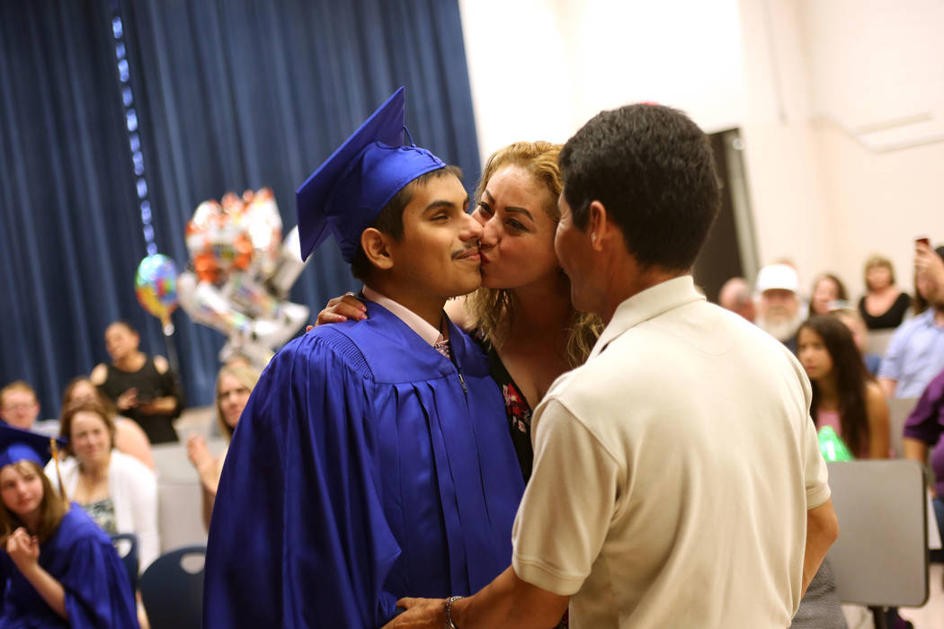 Karla Medina kisses her son Jose Gomez as his dad Jose Gomez watches during a graduation ceremony at Helen J. Stewart School, a special needs school, in Las Vegas, Wednesday, May 16, 2018. Rachel ...