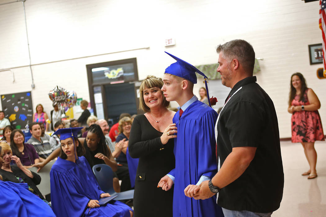 Julie Johnson stands stands with her son Mason Sandoval and his father Robert Sandoval during a graduation ceremony at Helen J. Stewart School, a special needs school, in Las Vegas, Wednesday, May ...