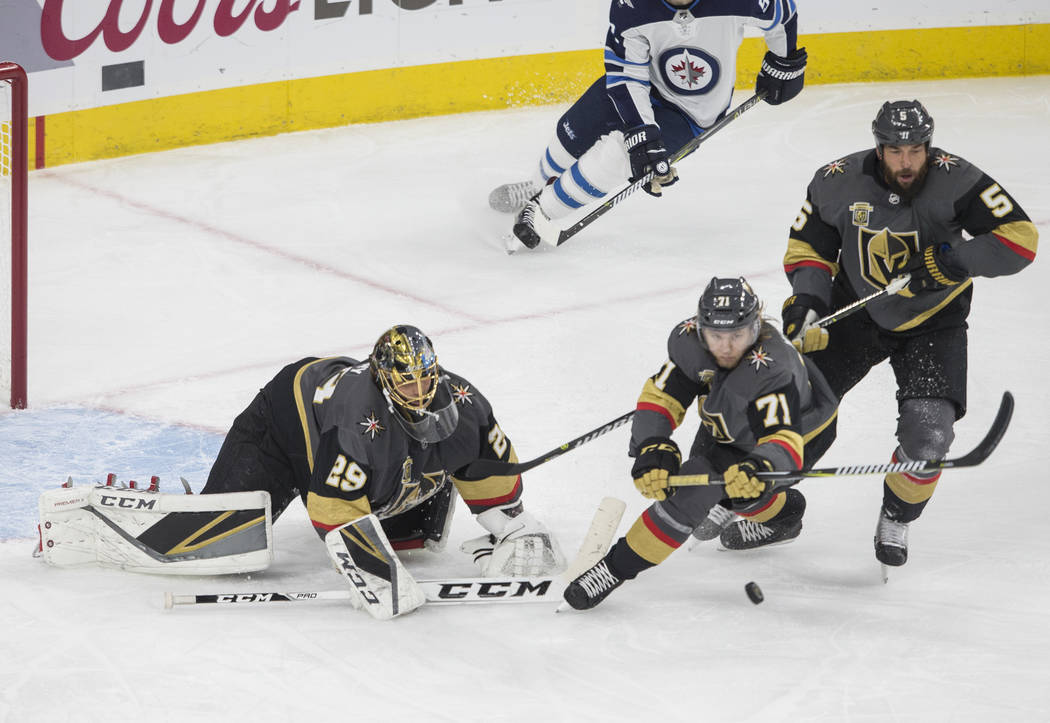 Golden Knights goaltender Marc-Andre Fleury (29) makes a save in the second period with the help of William Karlsson (71) and Deryk Engelland (5) during game three of Las Vegas' NHL Western Confer ...