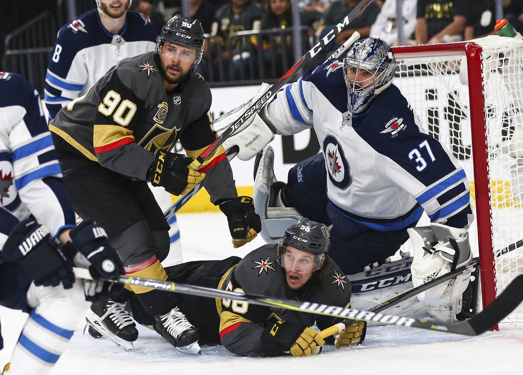 Golden Knights left wing Erik Haula (56) and Golden Knights left wing Tomas Tatar (90) watch the puck as Winnipeg Jets goaltender Connor Hellebuyck (37) defends during the first period of Game 3 o ...