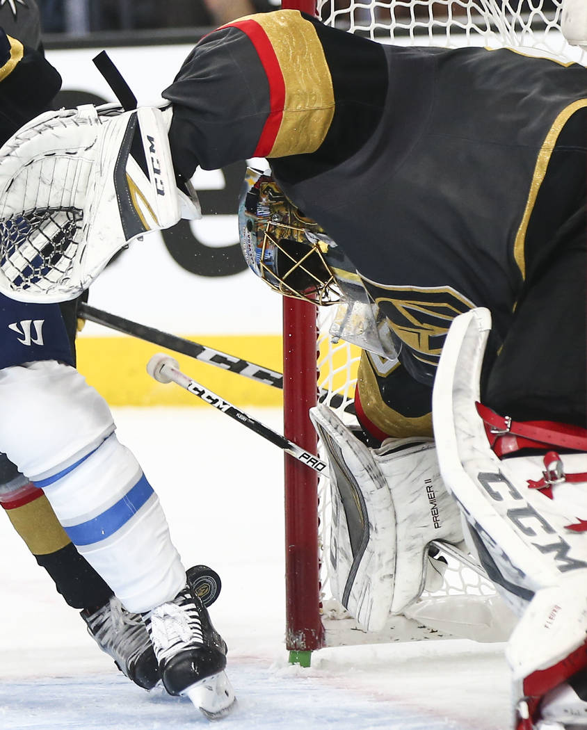 Golden Knights goaltender Marc-Andre Fleury (29) watches the puck after getting pushed into his goal during the second period of Game 3 of the NHL Western Conference finals hockey playoff series a ...