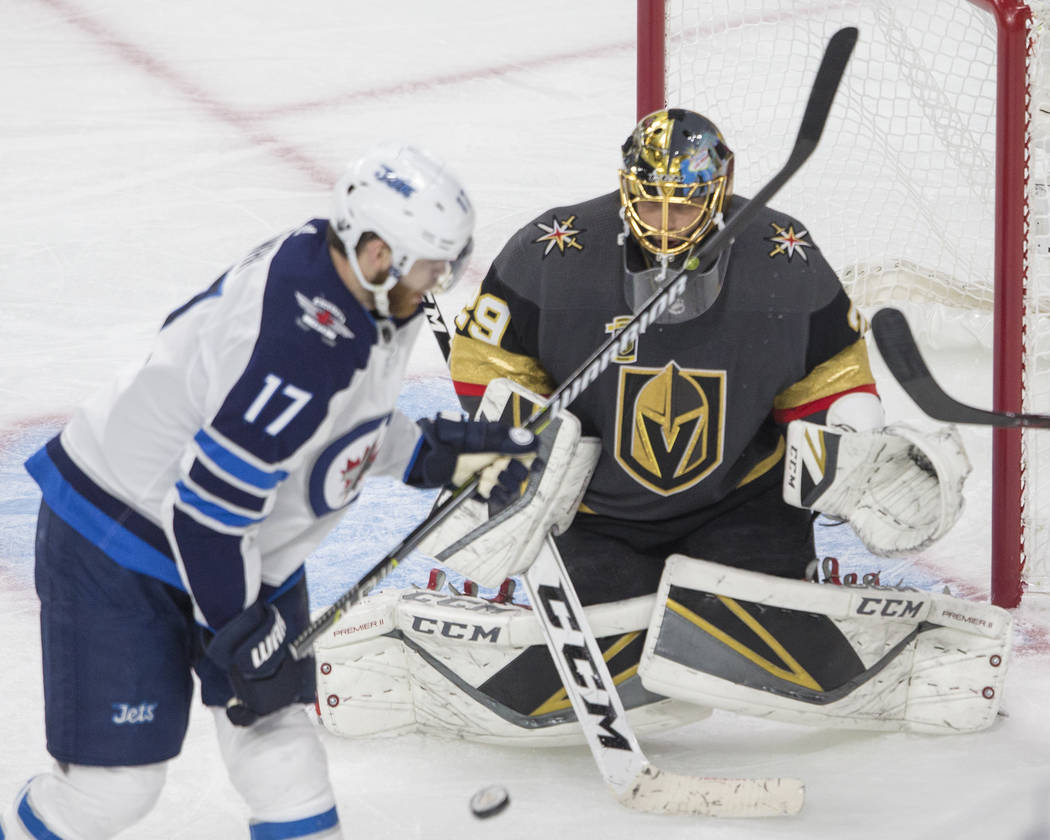 Golden Knights goaltender Marc-Andre Fleury (29) makes a save against Jets center Adam Lowry (17) in the third period during game three of Las Vegas' NHL Western Conference Finals matchup with Win ...