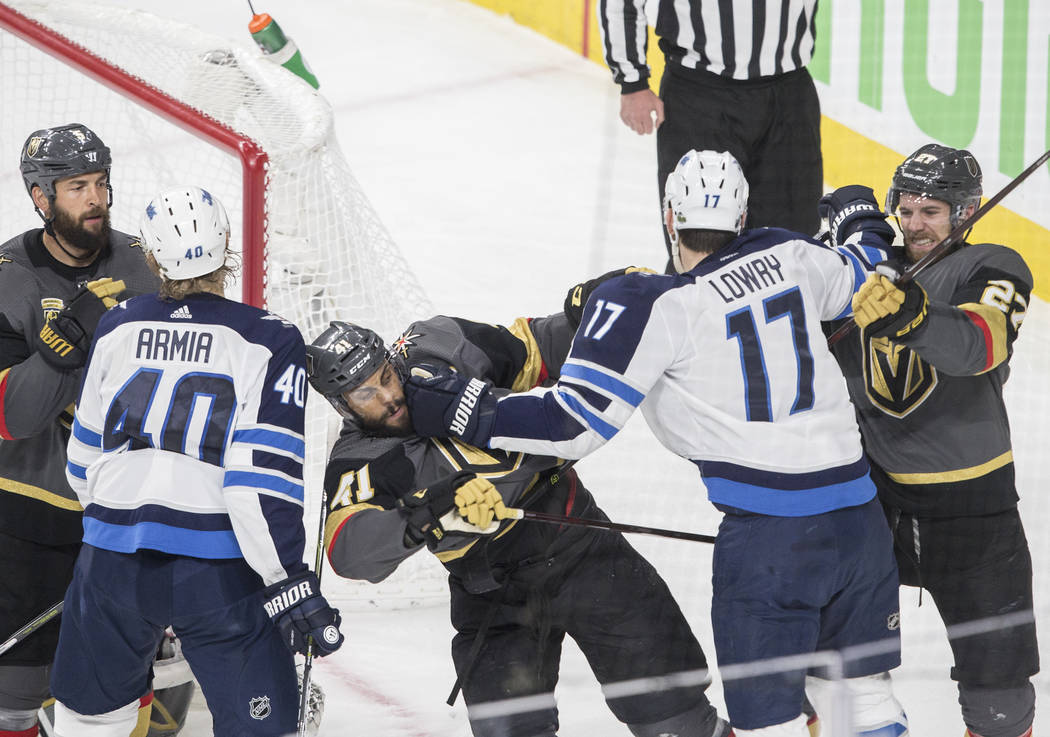 Golden Knights right wing Pierre-Edouard Bellemare (41) scuffles with Jets center Adam Lowry (17) in the third period during game three of Las Vegas' NHL Western Conference Finals matchup with Win ...