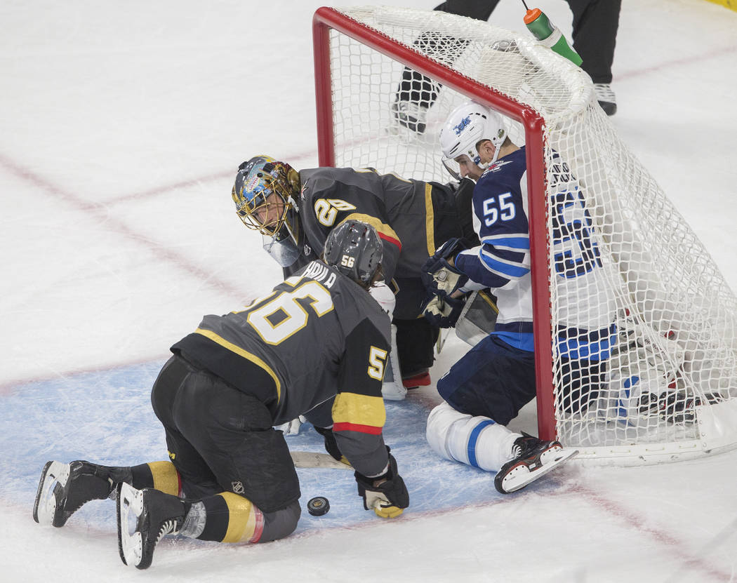 Golden Knights goaltender Marc-Andre Fleury (29) makes a save against Jets center Mark Scheifele (55) with the help from Golden Knights left wing Erik Haula (56) in the third period during game th ...