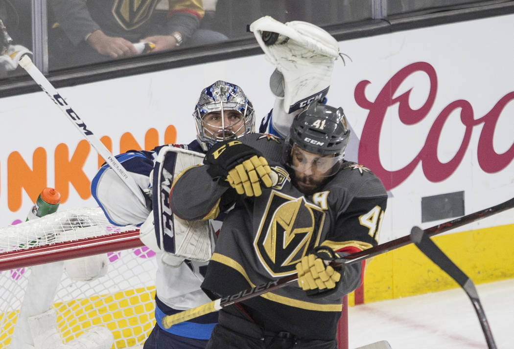 Golden Knights right wing Pierre-Edouard Bellemare (41) fights for position with Jets goaltender Connor Hellebuyck (37) during game three of Las Vegas' NHL Western Conference Finals matchup with W ...