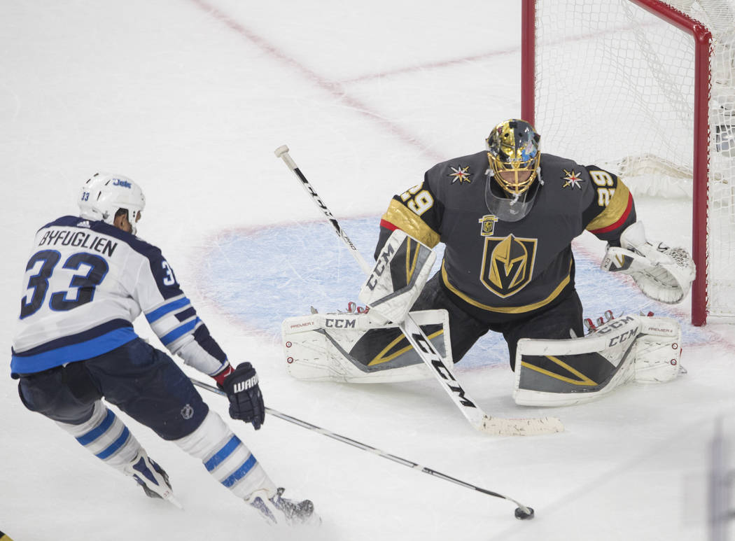Golden Knights goaltender Marc-Andre Fleury (29) makes a save against Jets defenseman Dustin Byfuglien (33) in the third period during game three of Las Vegas' NHL Western Conference Finals matchu ...