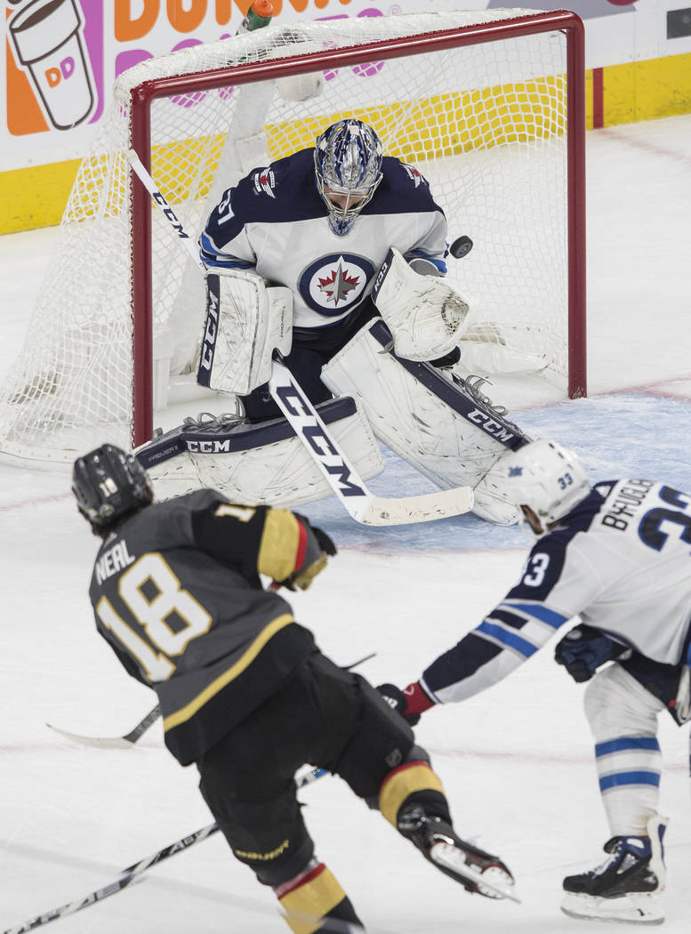 Golden Knights left wing James Neal (18) shoots on Jets goaltender Connor Hellebuyckus (37) in the third period during game three of Las Vegas' NHL Western Conference Finals matchup with Winnipeg ...