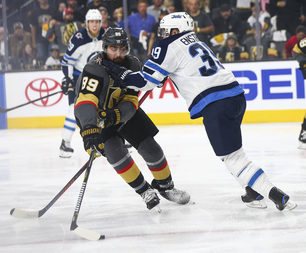 Winnipeg Jets defenseman Toby Enstrom (39) defends as Golden Knights right wing Alex Tuch (89) moves the puck during the first period of Game 3 of the NHL Western Conference finals hockey playoff ...
