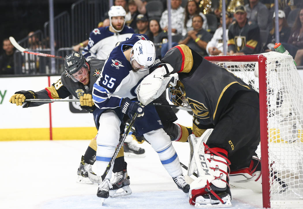 Golden Knights goaltender Marc-Andre Fleury (29) gets pushed into the goal by Winnipeg Jets center Mark Scheifele (55) during the second period of Game 3 of the NHL Western Conference finals hocke ...