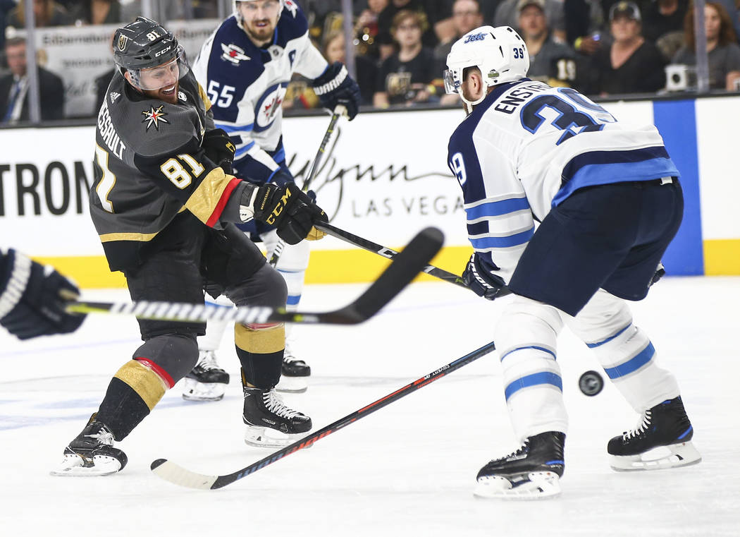 Golden Knights center Jonathan Marchessault (81) shoots between the legs of Winnipeg Jets defenseman Toby Enstrom (39) during the third period of Game 3 of the NHL Western Conference finals hockey ...