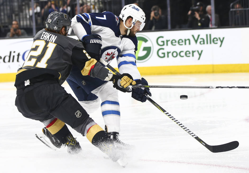 Golden Knights center Cody Eakin (21) and Winnipeg Jets defenseman Ben Chiarot (7) battle for the puck during the third period of Game 3 of the NHL Western Conference finals hockey playoff series ...