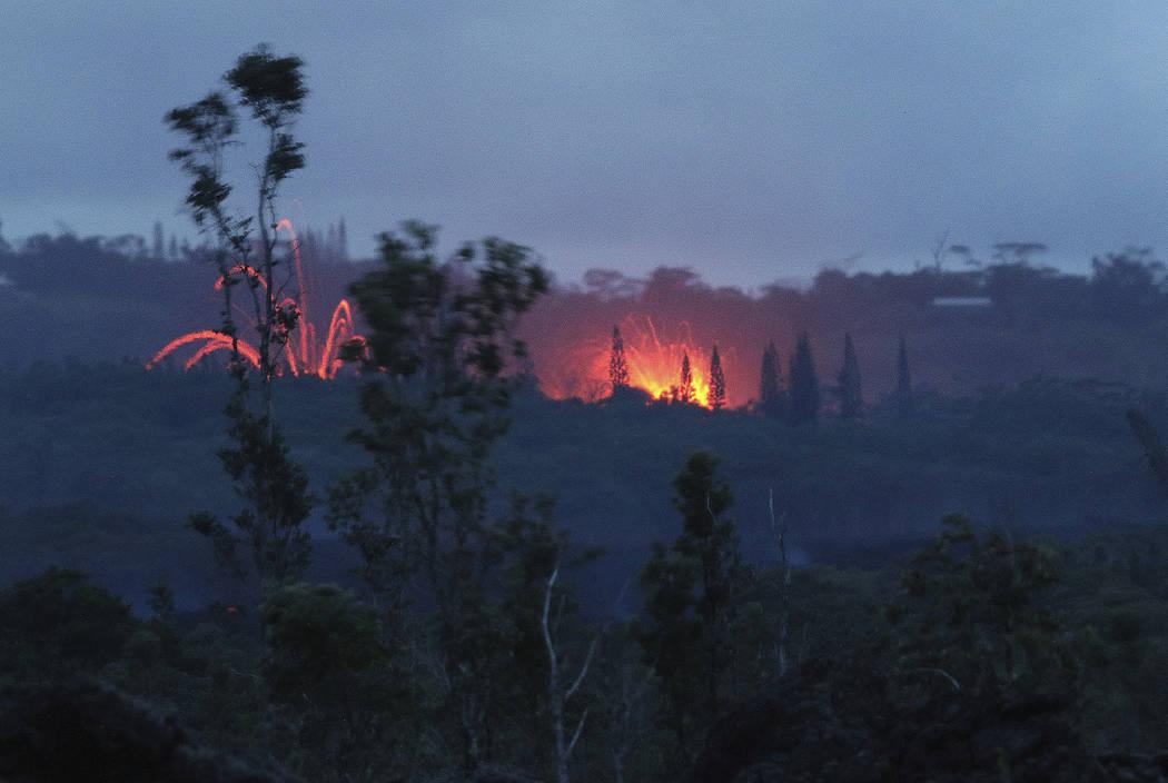 Lava shoots into the night sky from active fissures on the lower east rift of the Kilauea volcano, Tuesday, May 15, 2018, near Pahoa, Hawaii. (AP Photo/Caleb Jones)
