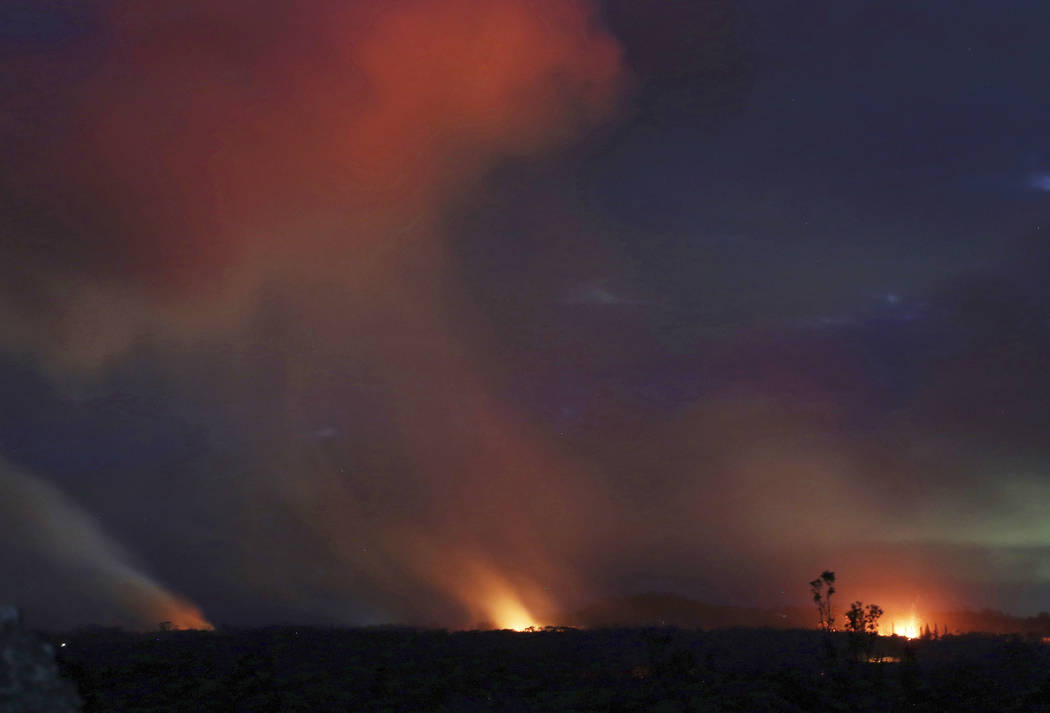 Lava shoots into the night sky from active fissures on the lower east rift of the Kilauea volcano, Tuesday, May 15, 2018 near Pahoa, Hawaii. (AP Photo/Caleb Jones)