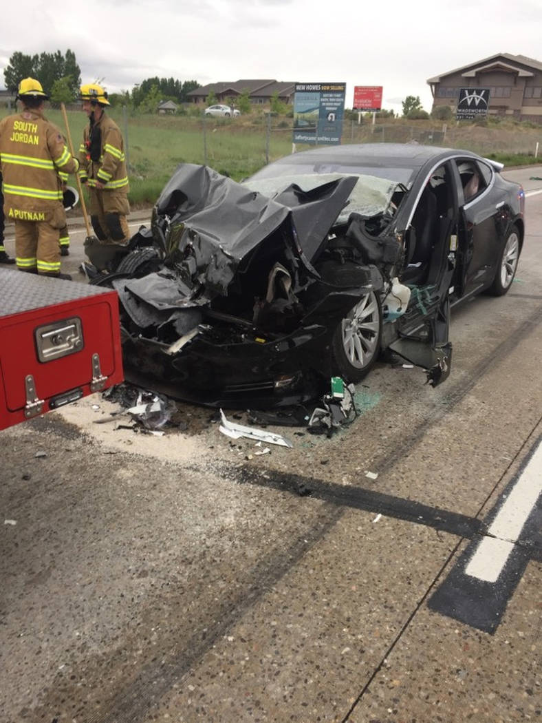 A traffic collision involving a Tesla Model S sedan with a Fire Department mechanic truck stopped at a red light is seen in South Jordan, Utah. (South Jordan Police Department via AP)