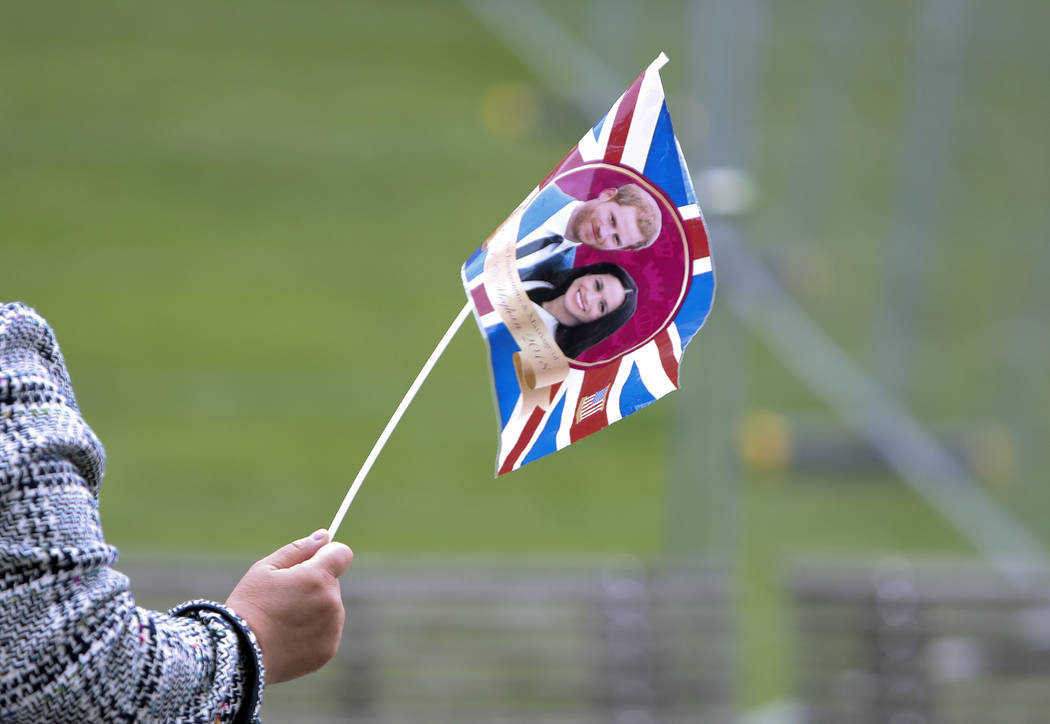 A tour guide leads her group of tourists using a flag with the faces of Britain's Prince Harry and his fiance Meghan Markle in Windsor, England, Wednesday, May 16, 2018. Preparations continue in W ...