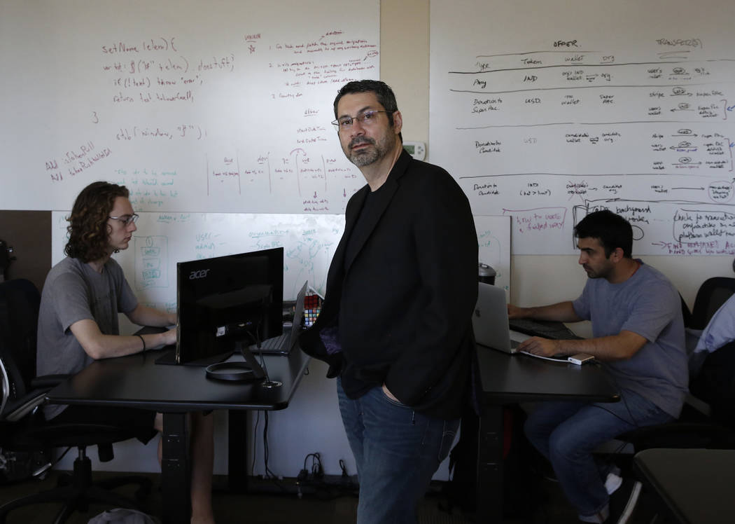 Rick Duggan, CEO at Concierge Software Design, poses for photo as Triston Jones, left, and Kandarp Dave, both senior software engineers, work on their project at their Las Vegas office on Friday, ...